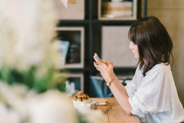 girl-using-smartphone-cafe-mobile-phone